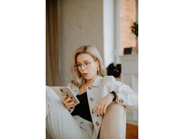 Woman in Beige Coat Holding Smartphone